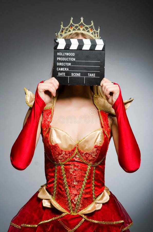 Queen in red dress. With movie clapboard royalty free stock photo