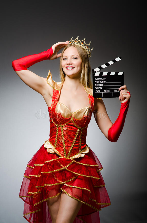 Queen in red dress. With movie clapboard stock photos