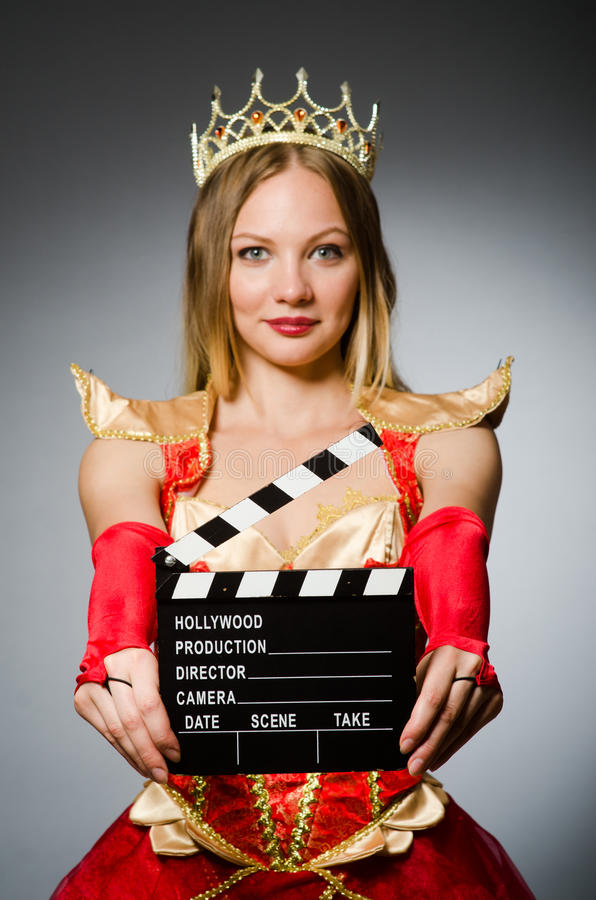 Queen in red dress. With movie clapboard royalty free stock image