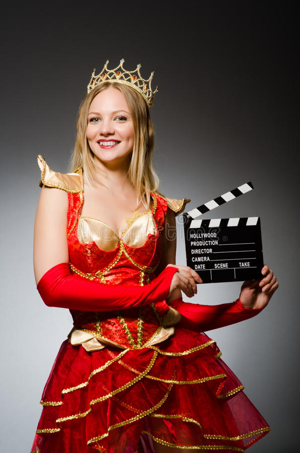 Queen in red dress. With movie clapboard stock photography