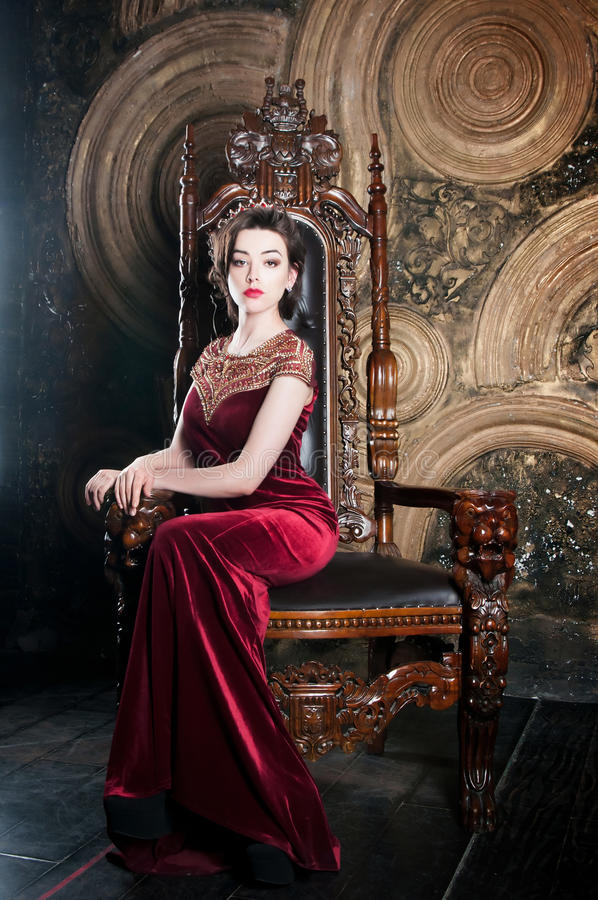 Queen in red dress sitting on throne. Symbol of power. Queen in red dress sitting on throne stock photo