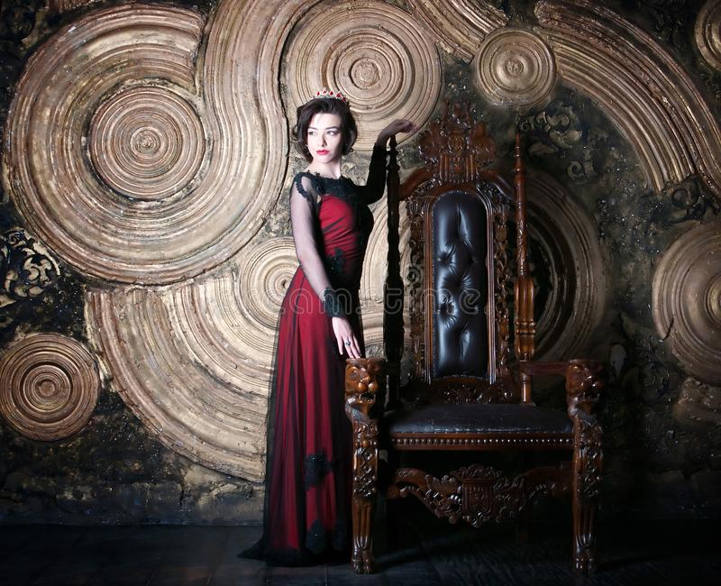 Queen in red dress sitting on throne. Symbol of power and wealth. Queen in red dress sitting on throne. Symbol of power royalty free stock photo