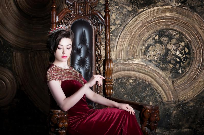 Queen in red dress sitting on throne. Symbol of power and wealth stock photos