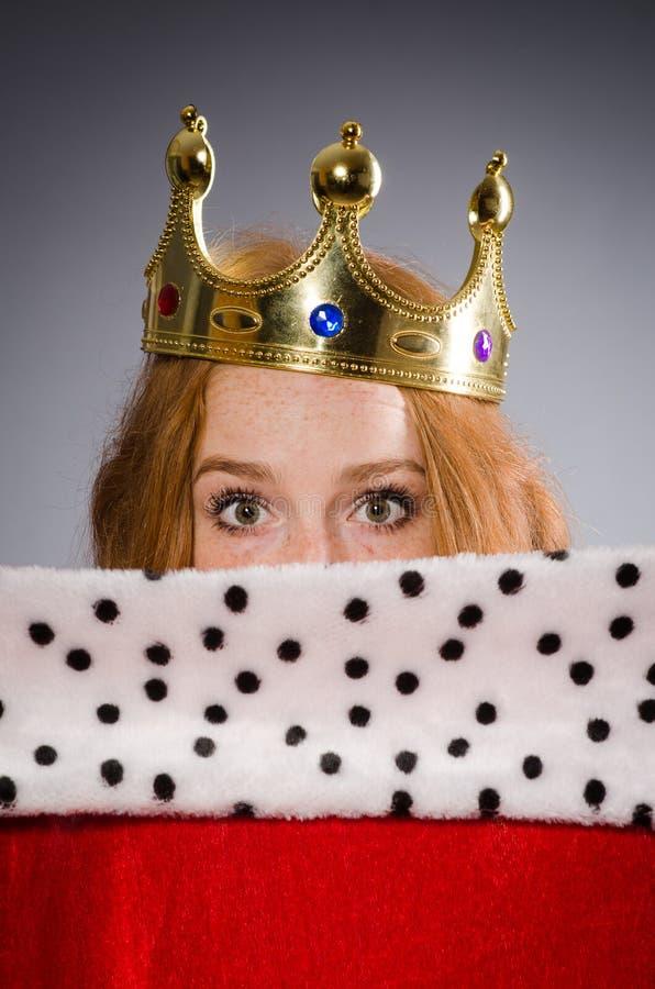 Queen in red dress. In studio stock images