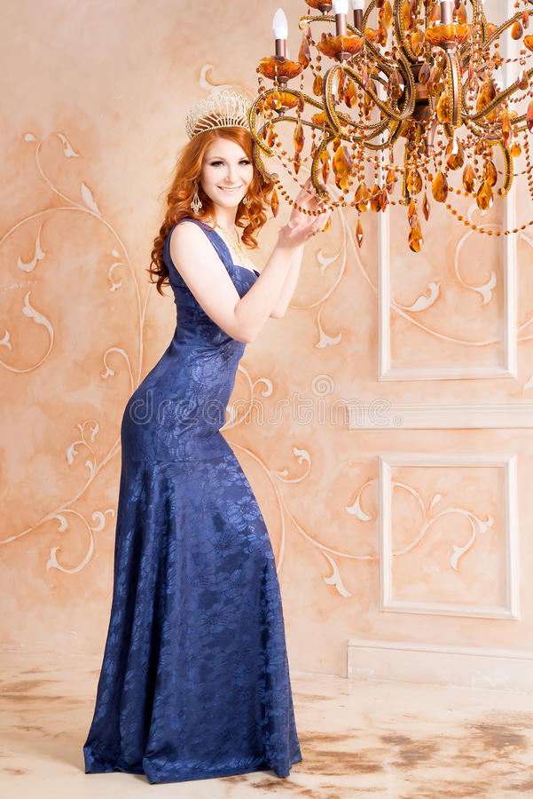 Queen, royal person with crown in blue dress. Chandelier royalty free stock images