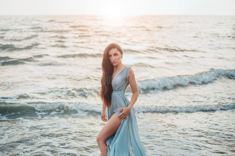 Queen of sea emerged from ocean and threateningly looks at world of dry land, long haired brunette beauty poses in long stock photography
