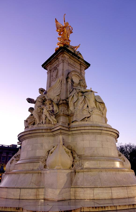 Queen Victoria Memorial Front. Front view of the marble Queen Victoria Memorial located in front of Buckingham Palace during dusk in London. The statues on the stock photos