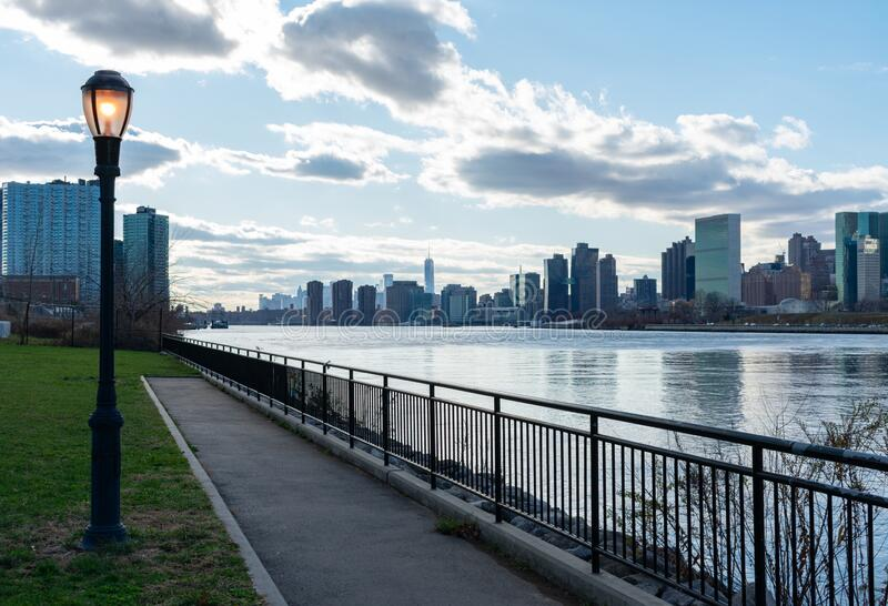 Queensbridge Park with a Street Light along the East River with the Manhattan Skyline in New York City stock image