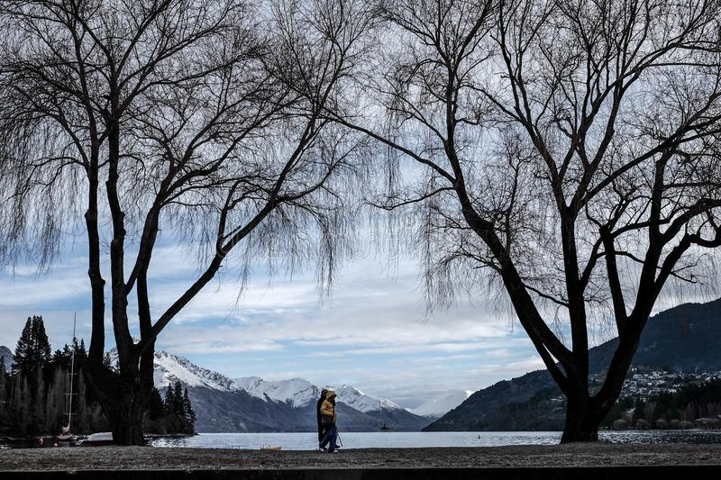Couple walking along queenstown park with beautiful background scenery royalty free stock images