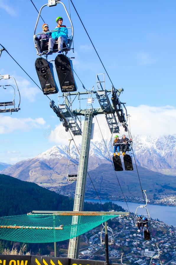 Chairlift is An elevated passenger which consists of a continuously circulating steel cable loop strung between two end terminals. Queenstown, New Zealand. - On royalty free stock photo