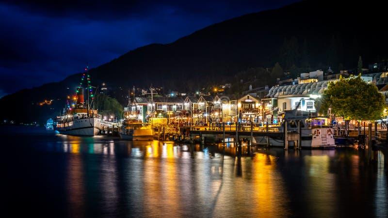 Queenstown, Nova Zelândia - porto da cidade na noite imagem de stock