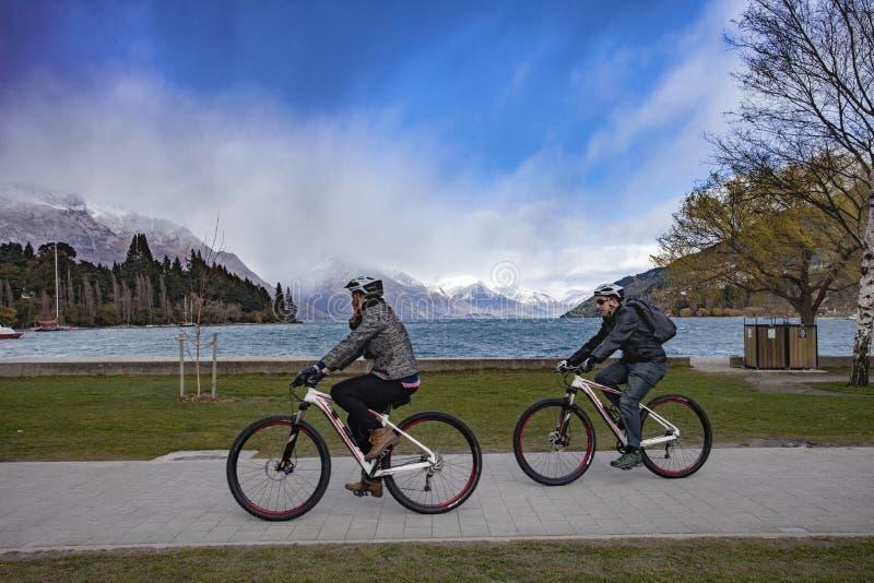 QUEENSTOWN NUEVA ZELANDA - 6 DE SEPTIEMBRE: bicicleta turística a del montar a caballo imagenes de archivo