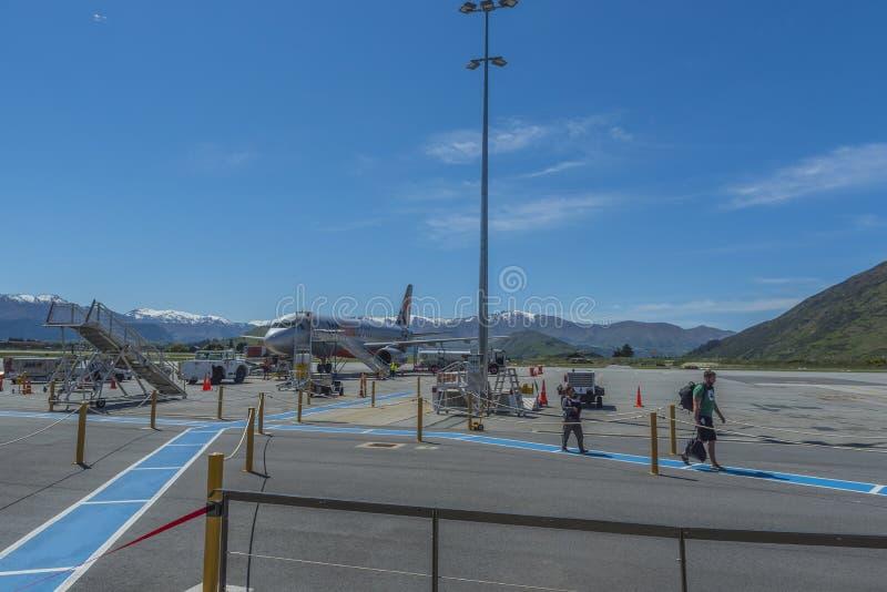QUEENSTOWN NYA ZEELAND - OKTOBER 10, 2018: Nivån på flygplatsen på en bakgrund av snöig berg Kopiera utrymme f?r text royaltyfria foton