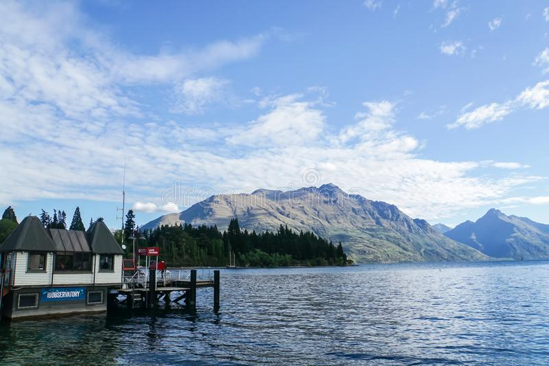 Queentown/Новая Зеландия - 2-ое декабря 2017: намочите офис обсерватории и гавань маломерного судна на стороне озера в солнечном  стоковое фото rf