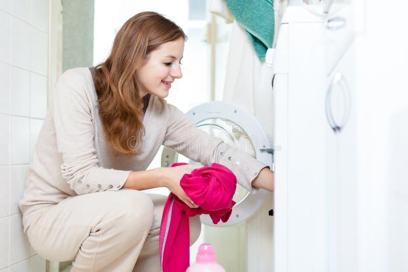 Quehacer doméstico: mujer joven que hace el lavadero fotografía de archivo