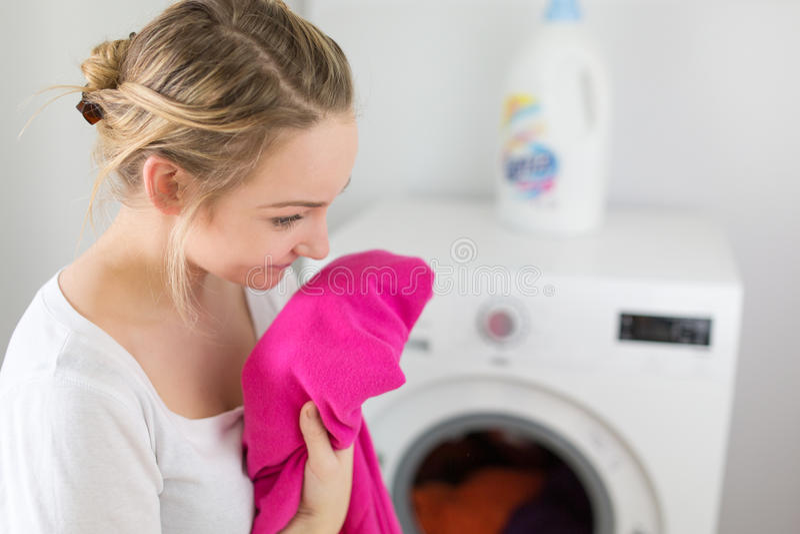 Quehacer doméstico: mujer joven que hace el lavadero imagen de archivo