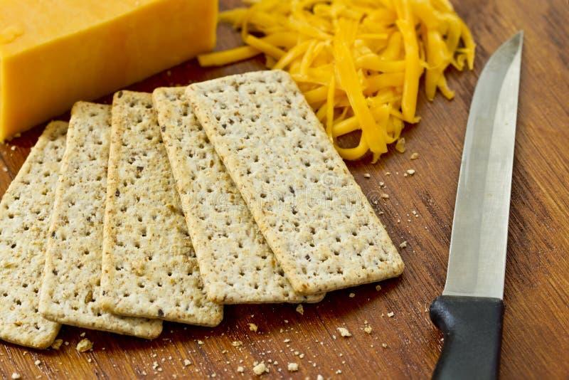 Queijo cheddar e biscoitos amarelos em um fundo de madeira fotos de stock royalty free