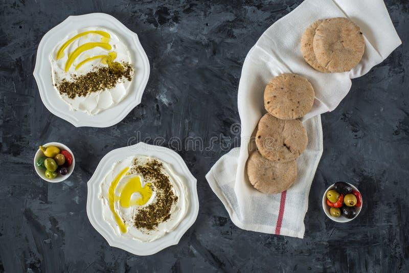 Queijo de cabra branco macio do Oriente Médio do labaneh de Labneh com azeite, azeitonas, za 'atar, limão, com pão do pão árabe s foto de stock