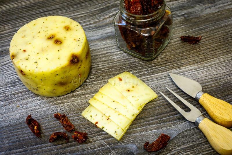 Queijo de cabra do fazendeiro com tomates secados, uma forquilha e faca do queijo, uma lata de tomates secados em uma tabela de m fotos de stock