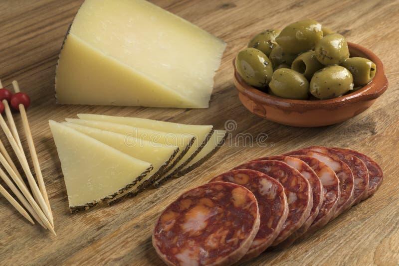 Queijo de Manchego do espanhol, salsicha do chouriço e azeitonas fotografia de stock