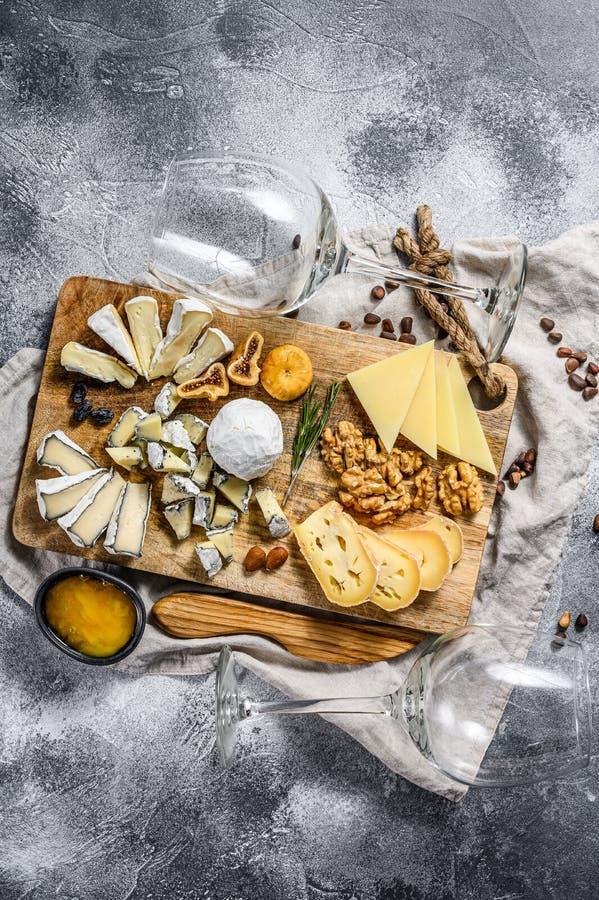 Queijo de mesa com queijo biológico francês, figos, frutos de casca rija com fundo cinzento Vista superior Arranque de queijo de  fotografia de stock royalty free