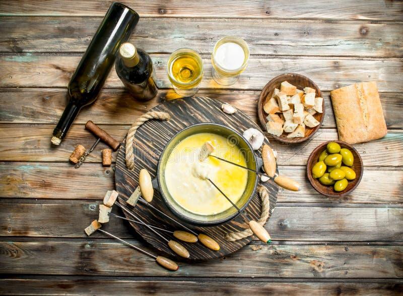 Queijo delicioso do fondue com azeitonas e vinho branco fotos de stock royalty free