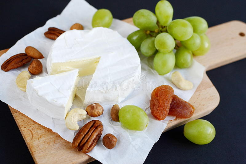 Queijo do brie com porcas, frutos secados e as uvas verdes na placa de madeira fotos de stock