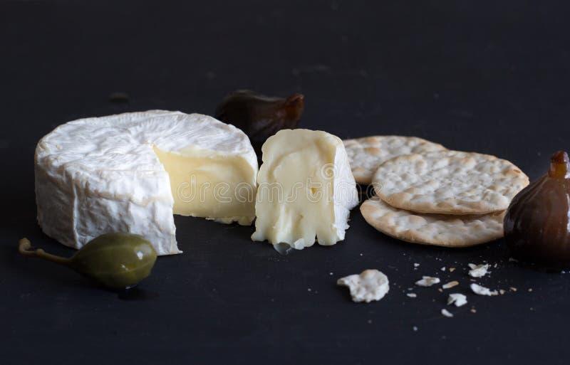 Queijo do camembert, figos, baga da alcaparra e biscoitos no backgr preto fotografia de stock