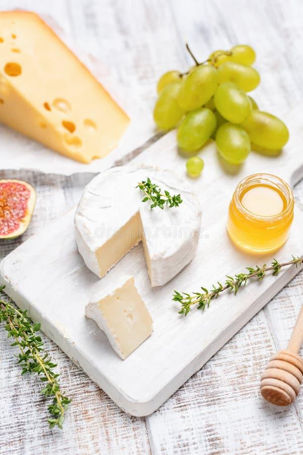 Queijo do camembert ou do brie na placa de madeira branca do serviço fotos de stock royalty free