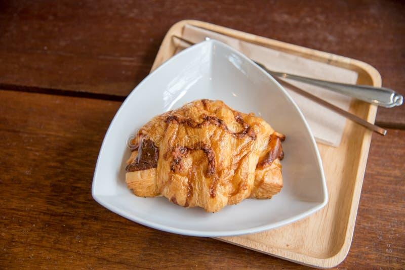 Queijo do presunto do croissant na placa branca do prato e da madeira com madeira imagens de stock