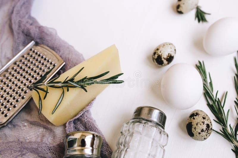 Queijo duro do Parmesão com alecrins, saleiro e pimenta de vidro, ovos e codorniz brancas da galinha, ralador e tela roxa da gaze imagem de stock