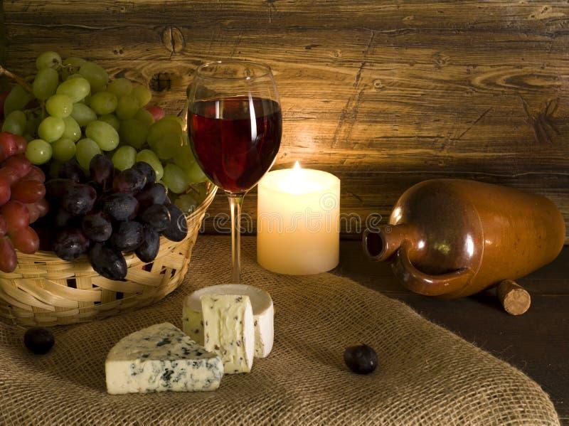 Queijo e uvas com vidro do vinho vermelho foto de stock royalty free