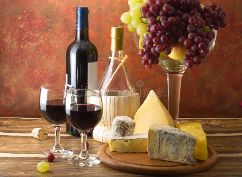 Queijo e uvas com vidros do vinho vermelho foto de stock