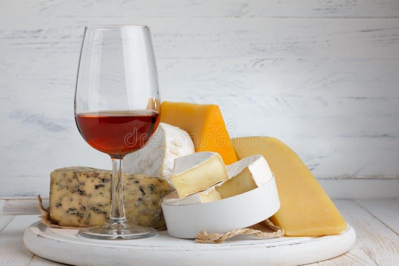 Queijo e vinho tinto na tabela de madeira imagens de stock royalty free