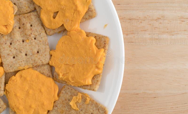 Queijo em biscoitos inteiros orgânicos do trigo em uma placa branca fotografia de stock royalty free