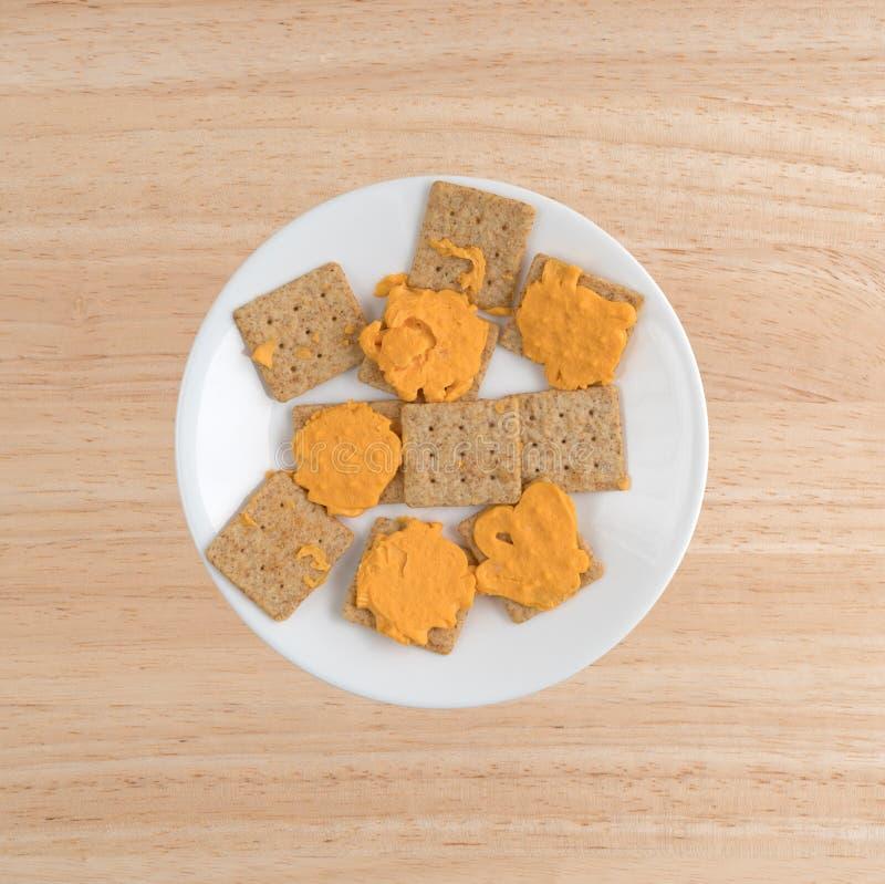 Queijo em biscoitos inteiros orgânicos do trigo em uma placa branca imagens de stock royalty free