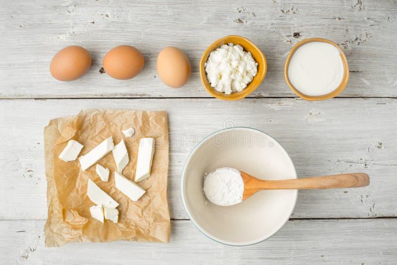 Queijo fresco diferente com iogurte e ovos na opinião de tampo da mesa de madeira branca fotos de stock royalty free