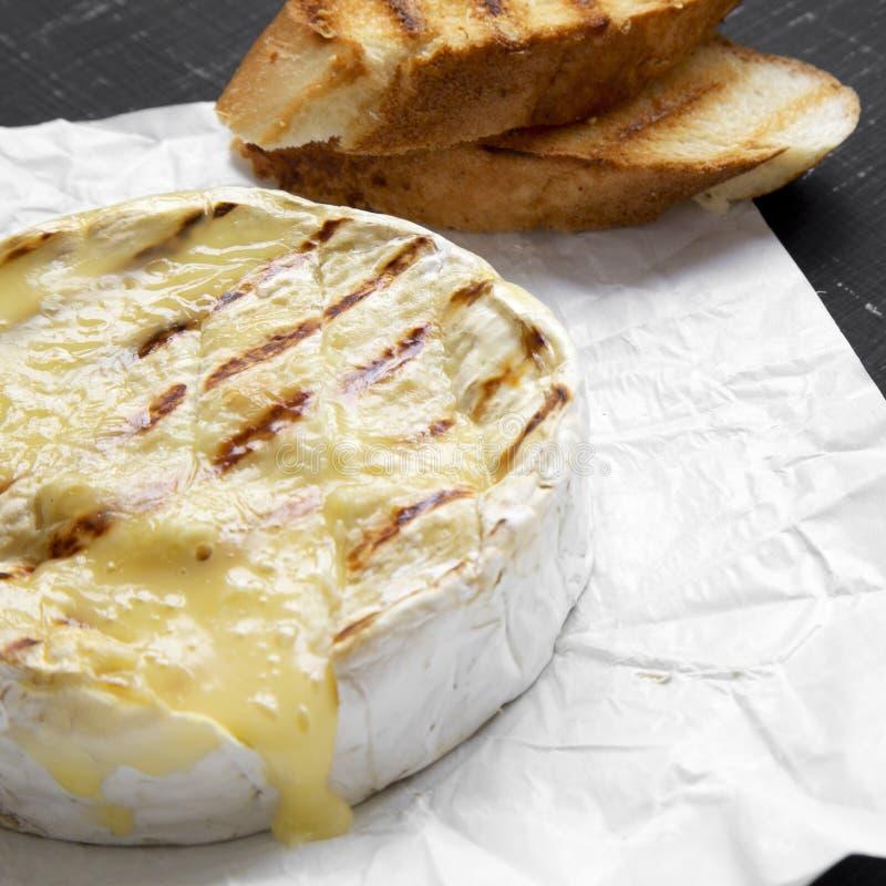 Queijo grelhado do camembert no papel com brindes em um fundo preto Alimento para o vinho Vista lateral closeup foto de stock