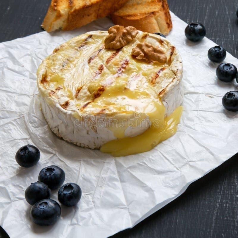 Queijo grelhado do camembert no papel com brindes, mirtilos e nozes em um fundo preto, close-up Alimento para o vinho fotografia de stock