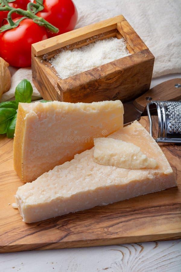 Queijo italiano original, queijo envelhecido do leite de vaca do Parmesão, partes e parmigiano-Reggiano raspado fotografia de stock