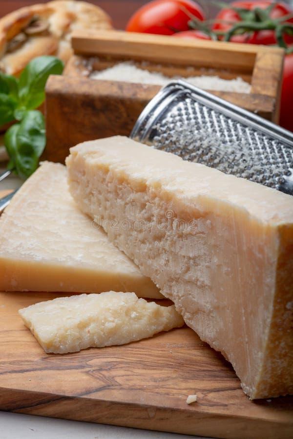 Queijo italiano original, queijo envelhecido do leite de vaca do Parmesão, partes e parmigiano-Reggiano raspado imagens de stock