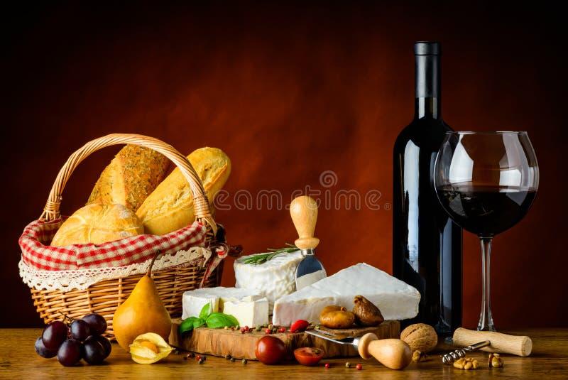Queijo macio, vinho tinto e bolo da cesta imagens de stock