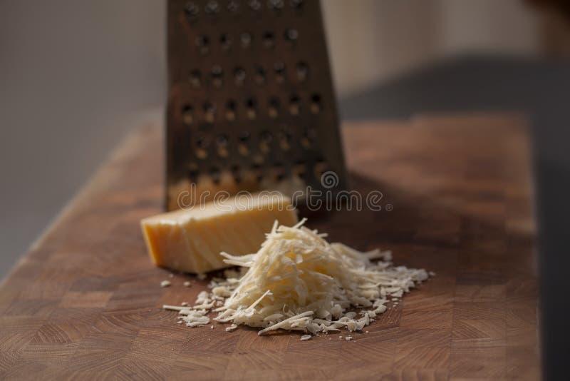 Queijo parmes?o italiano raspado na placa de desbastamento de madeira com um bloco de parmasan e em um ralador no fundo Feche aci imagem de stock