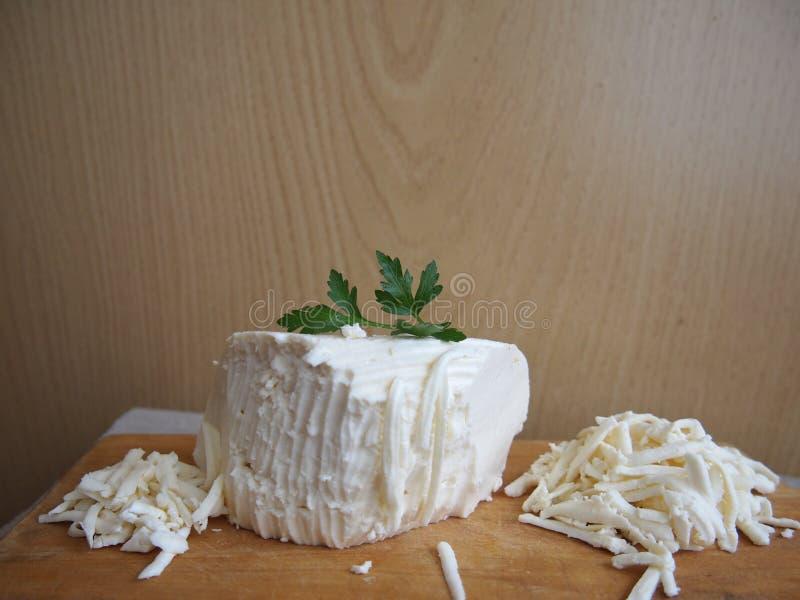 Queijo raspado dos carneiros em uma placa de madeira com um ramo da salsa foto de stock