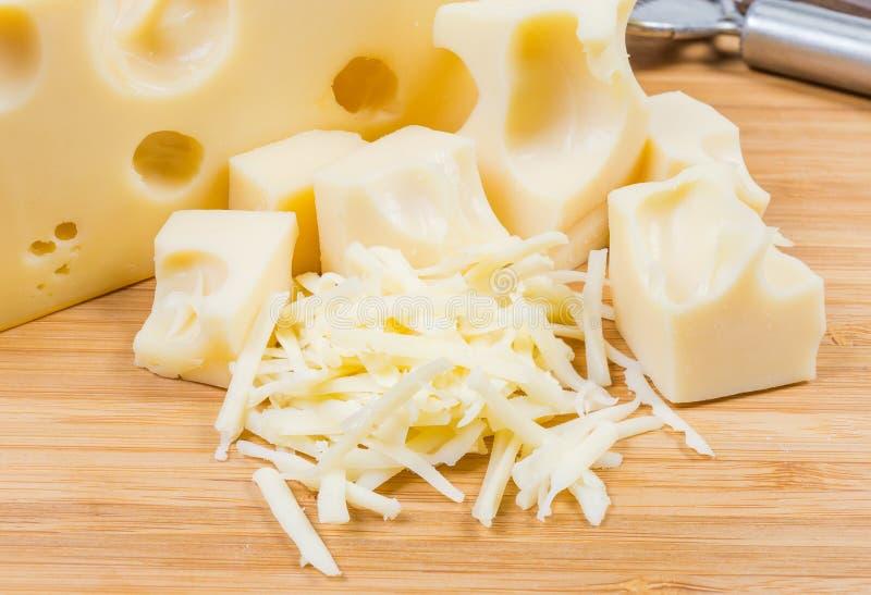 Queijo suíço raspado contra de fatias do mesmo queijo fotos de stock royalty free