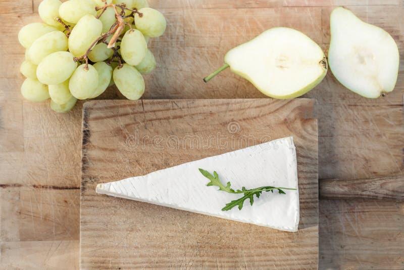Queijo, uvas e peras macios do brie da placa de queijo na tabela branca foto de stock royalty free