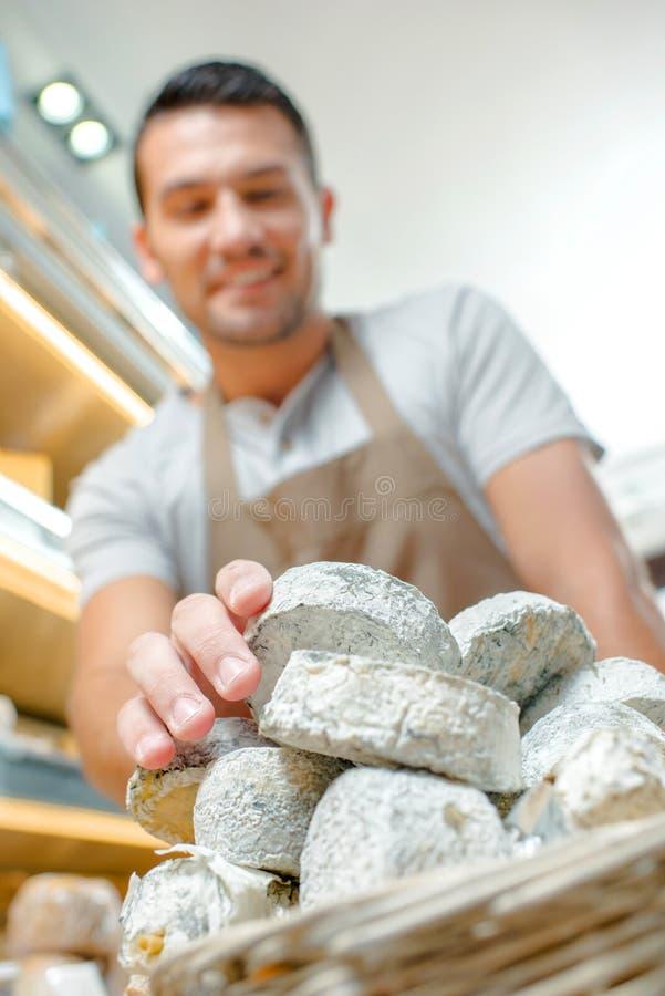 Queijos de equilíbrio da pilha do assistente de loja imagens de stock