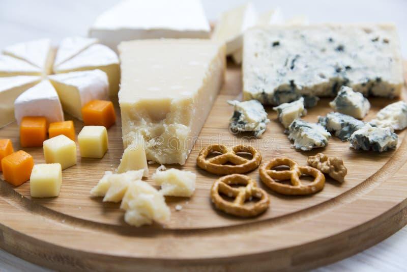 Queijos deliciosos: camembert, queijo azul, brie, Parmesão, mimolette e edam com pretzeis e nozes na placa de madeira redonda fotos de stock royalty free