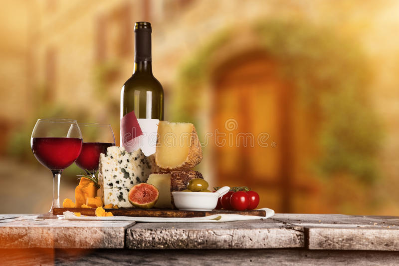 Queijos deliciosos com vinho na tabela de madeira velha imagem de stock
