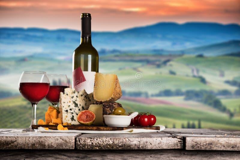 Queijos deliciosos com vinho na tabela de madeira velha fotografia de stock